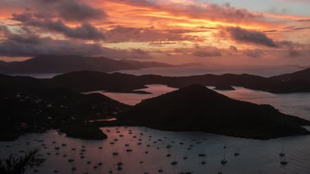 İngilizler : A time lapse of the sunrise over the Francis Drake Channel, the British Virgin Islands and Coral Bay, St. John.  Starting off dark the video transitions to beautiful pink and oranges then as the clouds clear, bright sunbursts.