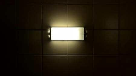 ürpertici : A creepy lamp flickers on a tile wall Stok Video