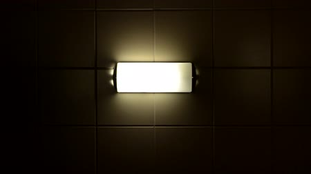 lampa : A creepy lamp flickers on a tile wall before being turned off.