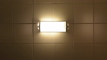 ürpertici : A creepy lamp mounted on a tile wall turns on with a lot of flickers. Stok Video