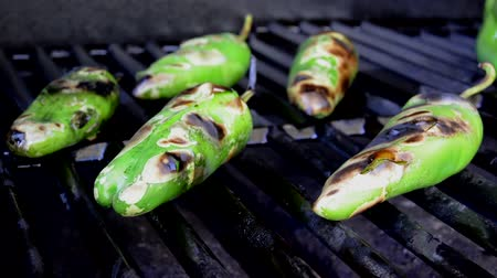 pieprz : Green chili peppers are roasting on a grill when the skin on the front left pepper rips open.