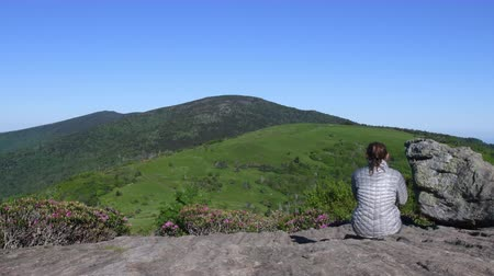 rhododendron : 4k Slide Left Behind Woman Sitting on Jane Bald Rocks during rhododendron bloom in June Stock Footage
