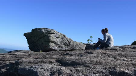bald mountain : 4K Tilt Up Woman Sits on Rocks and Plays on Phone instead of enjoying nature wide