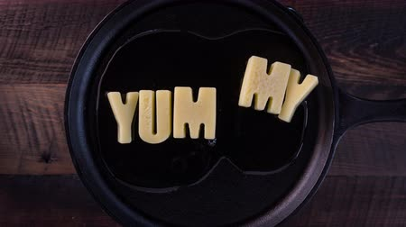 saute : Butter Words Yummy on Cast Iron Skillet Background Stock Footage