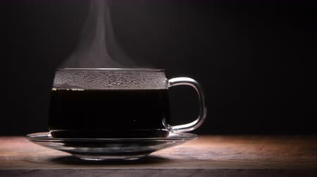 Steam Rises from Hot Coffee in Glass Cup on Left