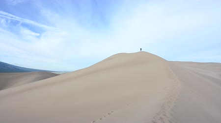 crest dune : Distant Woman Hikes on Crest of Dune on summer day