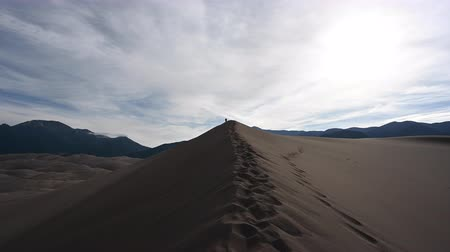 crest dune : Distant Woman Hikes Sand Dune early in the morning Stock Footage