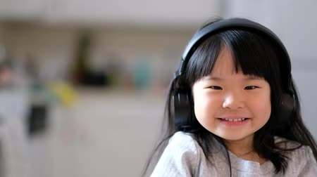 A young asian girl enjoying listening to music on her headphone and smiling 影像素材