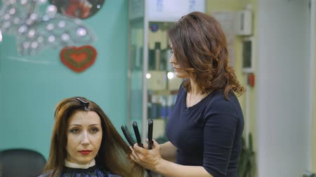 borbély : Hairdresser using straightener on beautiful woman hair in hair salon. Curling ripple