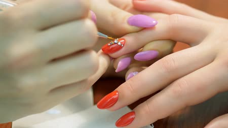 lakier do paznokci : Girl decorates nail rhinestones. Nail design with rhinestones closeup. Jobs manicurist.