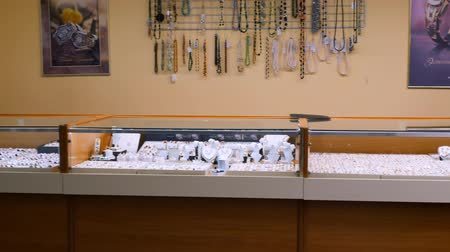 değerli : December 30, 2017, Mtsensk, Russia, Editorial - Showcase of a jewelry store. Silver and gold items with precious stones, necklaces on mannequins and various ornaments. Stok Video