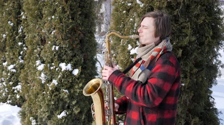 white shirt : saxophonist plays the saxophone, in winter