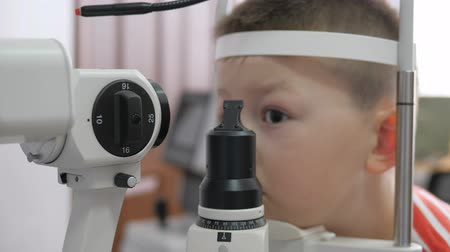 optyk : child in an ophthalmic clinic. Little boy looking at a tonometer in the eye exam Wideo