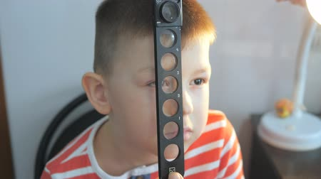 optyk : child in an ophthalmic clinic. Checking visual acuity with a line of ski-like