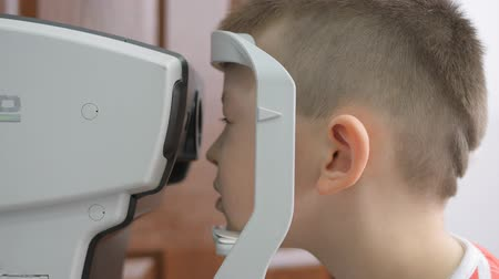 governante : child in an ophthalmic clinic. Little boy looking at a tonometer in the eye exam Vídeos