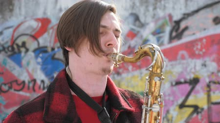 saxofonist : saxofonist speelt de saxofoon, in de winter Stockvideo