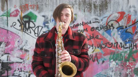 w : saxophonist plays the saxophone, in winter