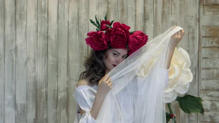 фигура : Girl posing in front of camera. young woman in a wreath of scarlet peonies on her head, dark long curly hair descends on the shallow shoulders.