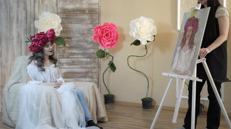 piwonia : artist draws a portrait from nature. The artist draws a portrait from nature. Floating camera focus, camera in motion. Beautiful model, with a wreath of scarlet peonies on his head, posing sitting in a white armchair. girl model admires her way on canvas. Wideo
