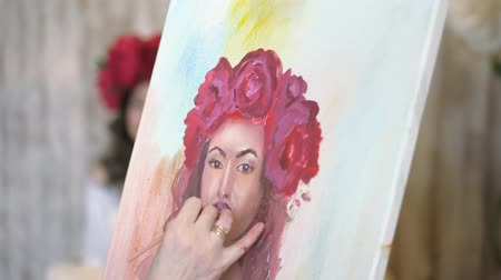 piwonia : artist draws a portrait from nature. The artist draws a portrait from nature. Floating camera focus, camera in motion. Beautiful model, with a wreath of scarlet peonies on his head, posing sitting in a white armchair. artist draws details of the models fa