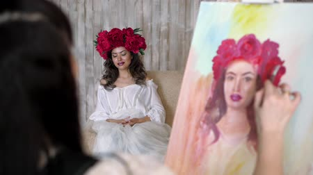 мольберт : artist draws a portrait from nature. The artist draws a portrait from nature. Floating camera focus, camera in motion. Beautiful model, with a wreath of scarlet peonies on his head, posing sitting in a white armchair. artist draws details of the models fa