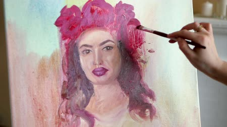 poz : artist draws a portrait from nature. The artist draws a portrait from nature. Floating camera focus, camera in motion. Beautiful model, with a wreath of scarlet peonies on his head, posing sitting in a white armchair. artist draws details of the models fa