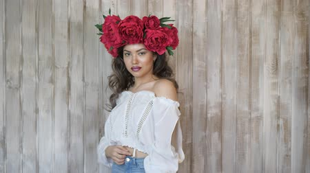 escarlate : Girl posing in front of camera. young woman in a wreath of scarlet peonies on her head, dark long curly hair descends on the shallow shoulders.