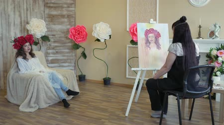 мольберт : artist draws a portrait from nature. The artist draws a portrait from nature. Floating camera focus, camera in motion. Beautiful model, with a wreath of scarlet peonies on his head, posing sitting in a white armchair. Стоковые видеозаписи