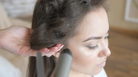 creative makeup : Makeup artist stylist works with model. hairdresser does the hair styling of the model. woman is working a styler with the girls long hair. The hairdresser makes curls on the girls straight hair. hair clip holds the hair curls of the model.
