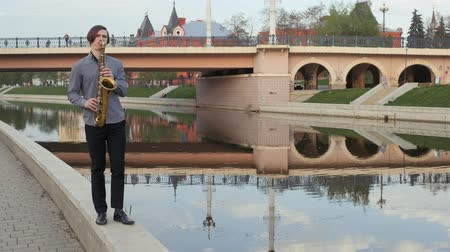 saxofon : young man plays the saxophone. The musician plays on the wind instrument, walks the parapet to the camera, the camera is in motion. Man moves on the narrow road. man on the background of the city bridge, river, temple and high-rise buildings.