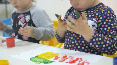 przedszkole : Childrens developing a game room. Emotions of young children during entertaining classes. children paint with finger paints on white sheets of paper. girl with a dirty red nose and face, straightens her hair with a hand and smiles sweetly.