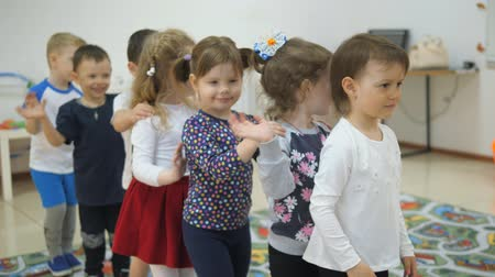детский сад : Childrens developing a game room. Emotions of young children during entertaining classes. Children put their hands on the neighbors shoulders and move happily one after another.