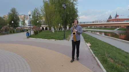saxofon : young man plays the saxophone. man on the background of the citys landscape blows into the pipe. musician goes to the camera along the embankment of the river.