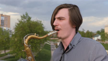 saxofon : young man plays the saxophone, closeup. man on the background of the citys landscape blows into the pipe.