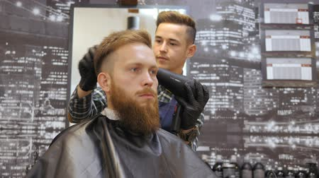 nape : Hairdresser for men. Barbershop. Caring for the beard. Barber with hair clipper works on hairstyle for bearded guy barbershop background. Hipster lifestyle concept. Barber with clipper trimming hair on nape of client. Hipster client getting haircut. Dryin Stock Footage