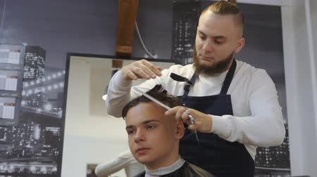 небритый : Hairdresser for men. Barbershop. Caring for the beard. Barber with hair clipper works on hairstyle for bearded guy barbershop background. Hipster lifestyle concept. Barber with clipper trimming hair on nape of client. Hipster client getting haircut. hairc Стоковые видеозаписи