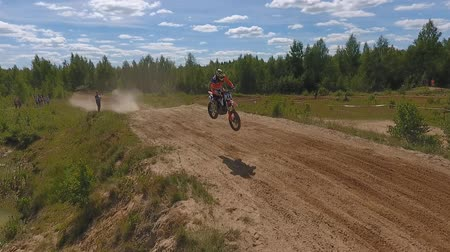 racers : 10 June 2018 Russian Federation, Bryansk region, Ivot - Extreme sports, cross-country motocross. Shooting with kvadrokoptera. Aerial and video in motion. The motorcyclist enters the turn on the race track. Dirt is flying from under the wheels. The machine