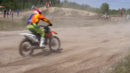 racers : June 10, 2018 Russian Federation, Bryansk region, Ivot - Extreme sports, cross motocross. The motorcyclist enters the turn on the race track. Dirt is flying from under the wheels. The machine overcomes obstacles. Athletes fly through the air. slow motion