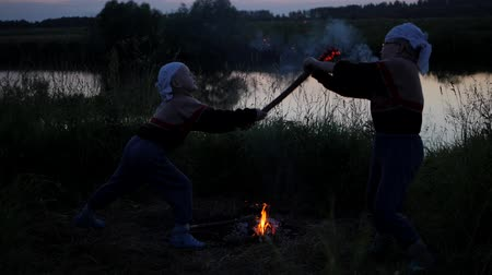 coals : sparks from burning sticks. Battle of children to burning dubankah. children fight against the background of the river. Coals from burning sticks scatter in different directions. Slow motion Stock Footage