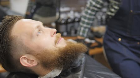 nape : Hairdresser for men. Barbershop. Caring for the beard. Barber with hair clipper works on hairstyle for bearded guy barbershop background. Hipster lifestyle concept. Barber with clipper trimming hair on nape of client. Hipster client getting haircut. haird Stock Footage