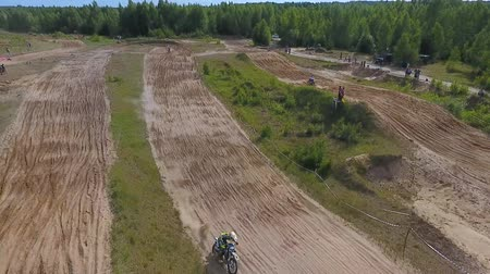 yarışçı : 10 June 2018 Russian Federation, Bryansk region, Ivot - Extreme sports, cross-country motocross. Shooting with kvadrokoptera. Aerial and video in motion. Camera in motion. Tracking a man riding a motorcycle. The motorcyclist enters the turn on the race tr Stok Video