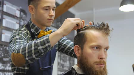 barber scissors : Hairdresser for men. Barbershop. Hair care. Hairdresser with a haircut works for a hairstyle for a bearded guy. The concept of a hipster lifestyle. The hairdresser cuts the hair on the back of the client. Customer Hipster gets a haircut. a hairdresser in