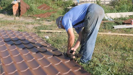 dekarz : Work with roofing material. roof of metal. Cutting profile metal electric bulgarian. Sparks fly from under the metal circle of the hand cutting tool. sheet of roofing material lies on green grass. Cutting sheet iron. Wideo
