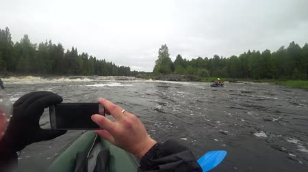 remoção : River rafting kayaking. Overcoming water rapids by boat. Rowing paired paddle. Extreme sports. Water sports. Shooting Action camera. man on the boat shoots the water passage through the athletes on the phone.