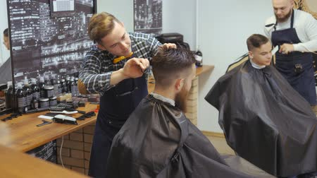 barber scissors : Hairdresser for men. Barbershop. Caring for the beard. Barber with hair clipper works on hairstyle for bearded guy barbershop background. Hipster lifestyle concept. Barber with clipper trimming hair on nape of client. Hipster client getting haircut. haird Stock Footage