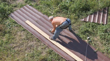 dekarz : Work with roofing material. roof of metal. Cutting profile metal electric bulgarian. Sparks fly from under the metal circle of the hand cutting tool. sheet of roofing material lies on green grass. View from a height. Cutting sheet iron.