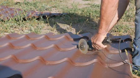 мастер на все руки : Work with roofing material. roof of metal. Cutting profile metal electric bulgarian. Sparks fly from under the metal circle of the hand cutting tool. sheet of roofing material lies on green grass. Cutting sheet iron. Стоковые видеозаписи