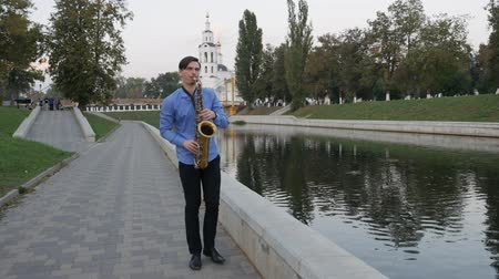 trąbka : Saxophonist plays the trumpet. City Embankment. man with a whiskered up mustache playing a musical instrument on the streets of the city.