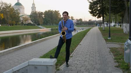 saxofon : Saxophonist plays the trumpet. City Embankment. man with a whiskered up mustache playing a musical instrument on the streets of the city.