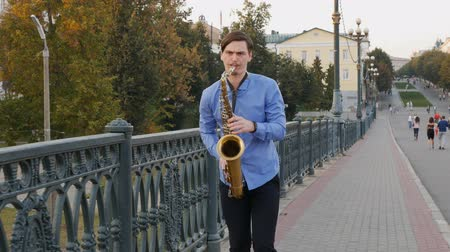 saxofon : Saxophonist plays the trumpet. City Embankment. man with a whiskered up mustache playing a musical instrument on the streets of the city. musician stands on the bridge and plays a musical instrument.